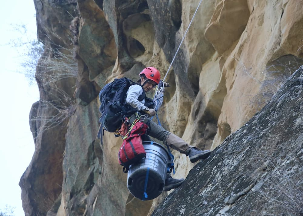 Person scaling a cliff